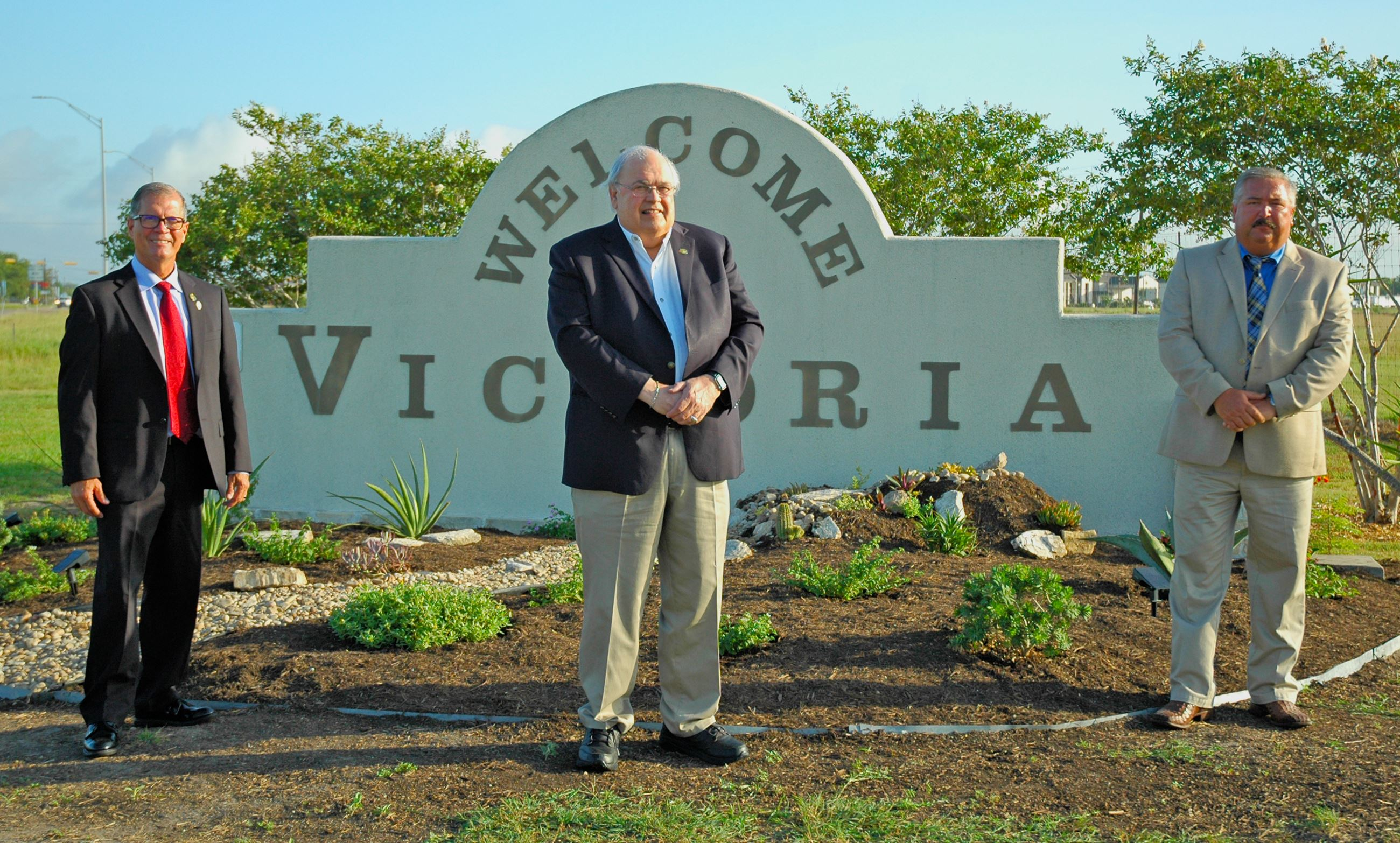 "Councilman, mayor and Environmental Services director in front of ""Welcome to Victoria"" sign"
