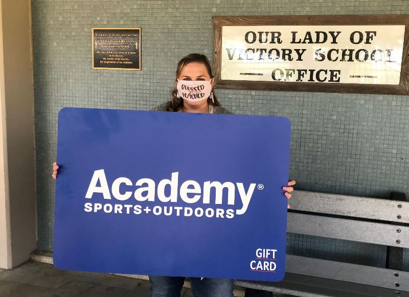 Woman holds giant Academy Sports and Outdoors gift card