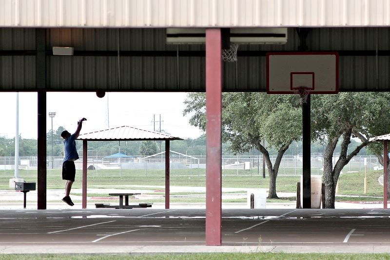 A silhouetted basketball player shoots a basket at an empty basketball court.