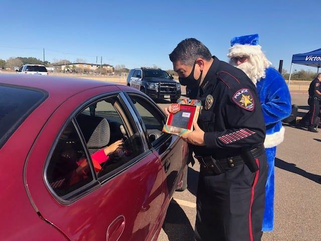 Uniformed police chief hands a gift-wrapped Etch-a-Sketch to a child through a car window.