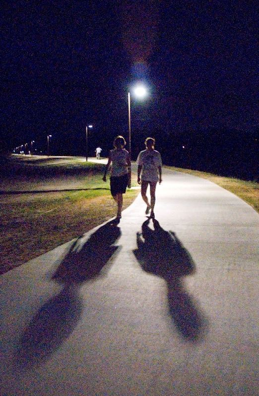 Two people walking along the Lone Tree Creek Hike and Bike Trail at night