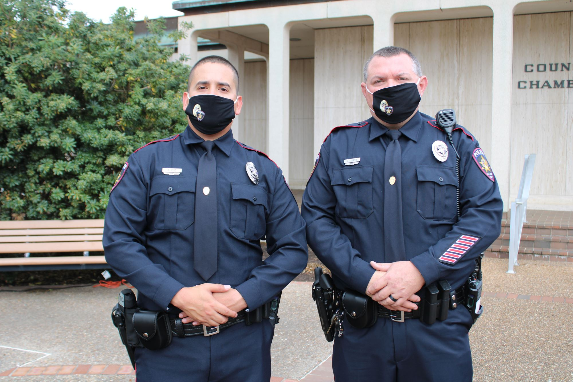 Two uniformed officers wearing facial coverings stand side by side.