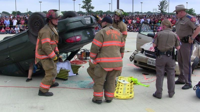 Fire fighters lifting a car during an educational class about drunk driving