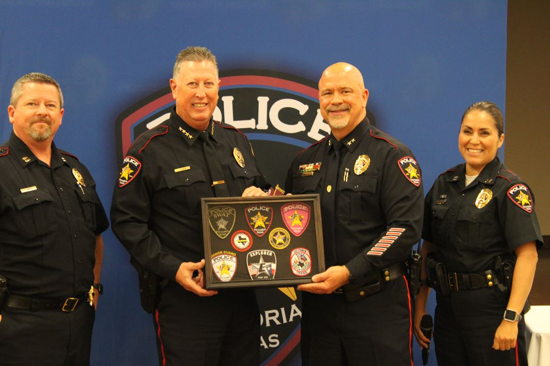 Police officers hold display case of patches