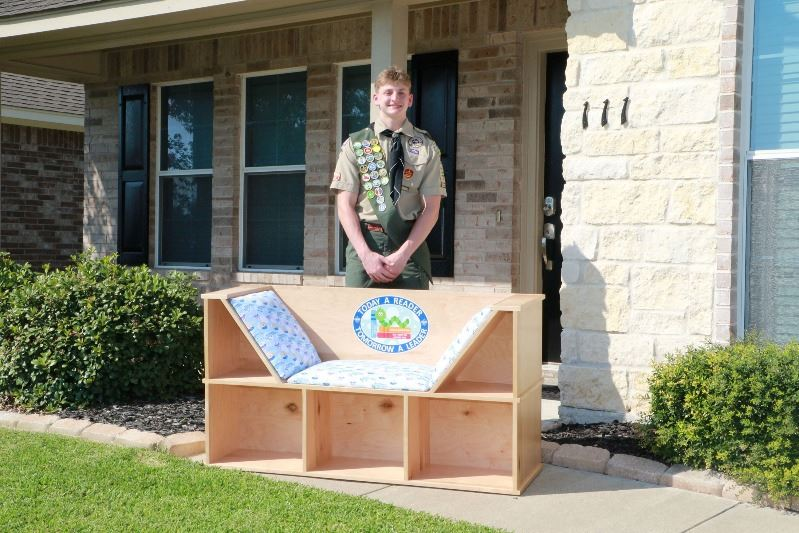 Teen in Boy Scout uniform poses with a wooden reading nook that features bookshelves.