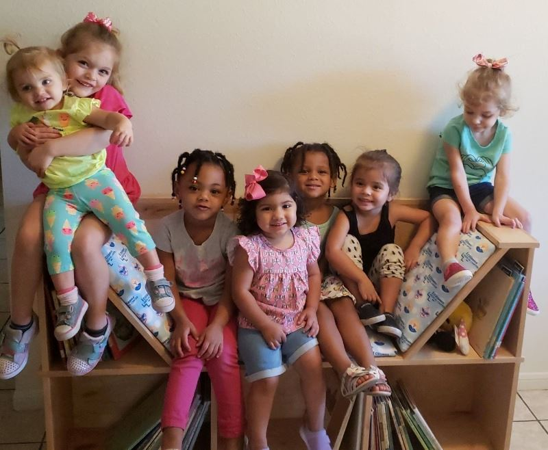 Preschool children pose with wooden reading nook that contains shelves full of books.