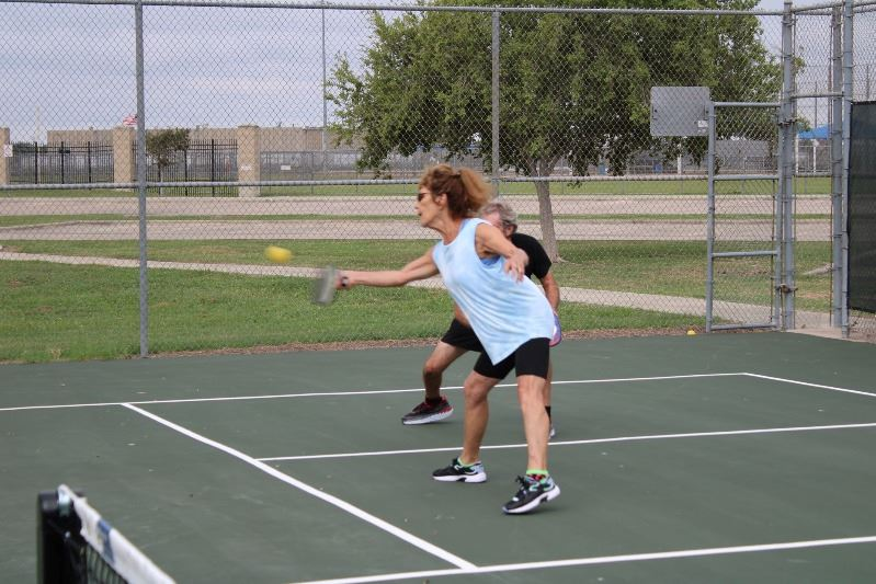 A woman playing pickleball reaches to hit the ball.