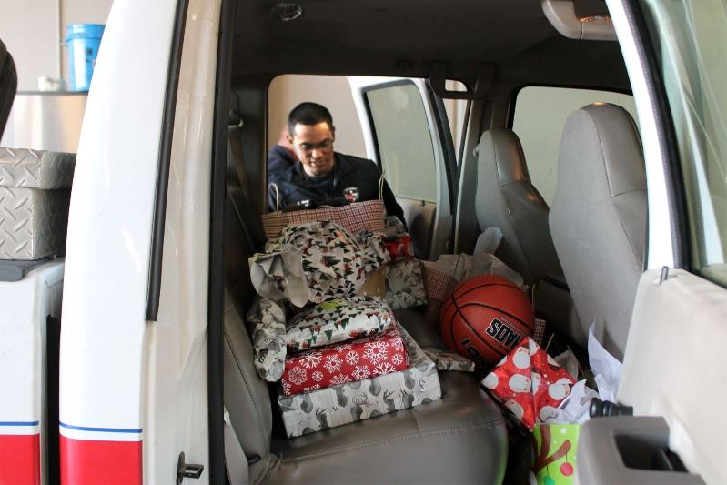 Man places gift bag in truck backseat alongside stacked gift boxes, bags and a basketball.