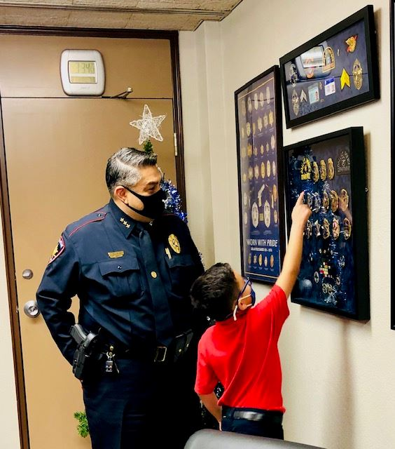Boy points to a badge in a framed badge display while police chief looks on.