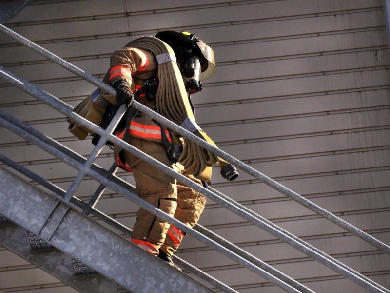 Fire fighter walking down stairs with a hose